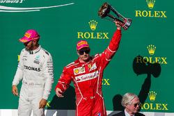 Third place Kimi Raikkonen, Ferrari celebrates on the podium with the trophy