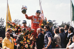 Race winner Niki Lauda, Ferrari, celebrates with second place Clay Regazzoni, Ferrari and third place Jacques Laffite on the podium