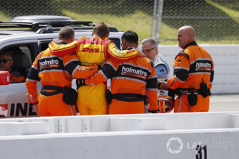 Сотрудники команды безопасности Holmatro помогают Райану Хантер-Рею, Andretti Autosport Honda, покинуть машину после аварии