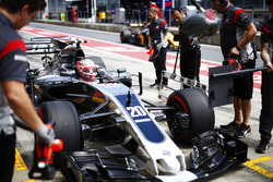 Kevin Magnussen, Haas F1 Team VF-17, stops in his pit as a Renault Sport F1 Team passes by