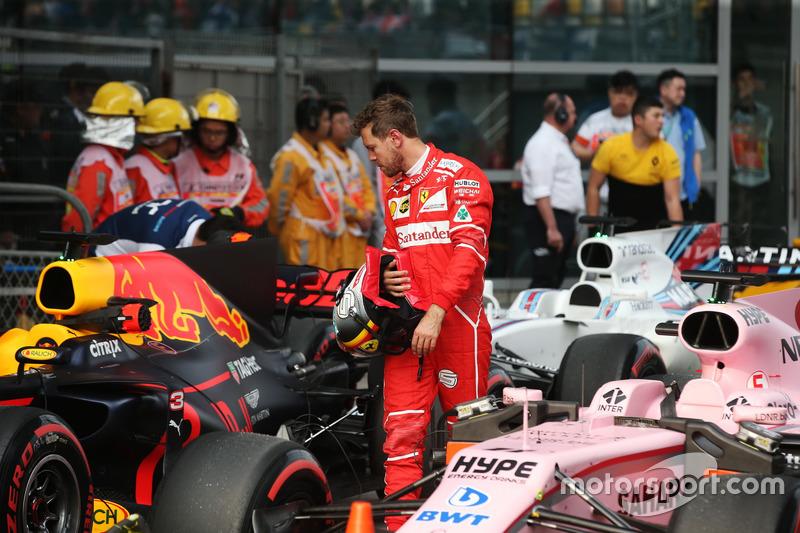 Гонщик Ferrari Себастьян Феттель осматривает Red Bull Racing RB13 в закрытом парке