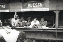 """Zusammen mit Freunden verbringt Hans Rüesch 1934 eine Trainingspause in den Boxen von Bern. Vor ihm steht der Maserati 4CS, an dessen Steuer er das Rennen der """"Kleinvolumigen Rennwagen"""" (bis 1500 cm3) bestreiten wird"""