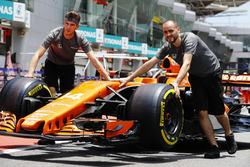 Les mécaniciens McLaren bougent la voiture de Fernando Alonso, McLaren MCL32