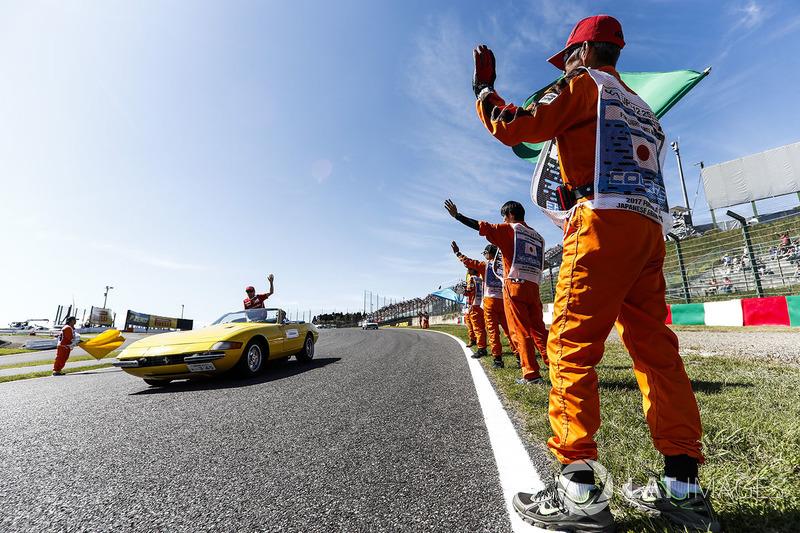 Marshals line the track as Kimi Raikkonen, Ferrari, passes in the drivers parade