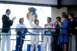 Exhausted race winner Gilles Villeneuve, Ferrari, centre, takes the applause as Jaques Laffite, Ligier, left, and John Watson, McLaren, right, look on