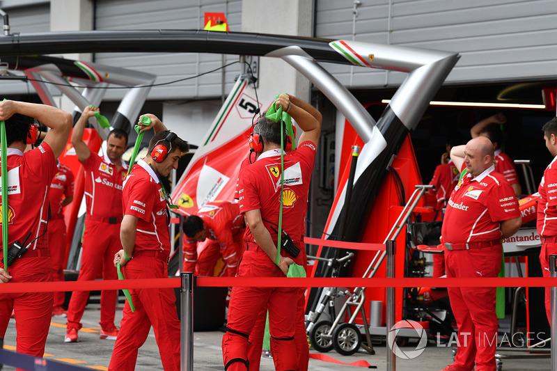 Ferrari mechanics exercising in the pitlane