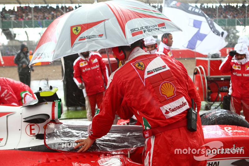 Un meccanico Ferrari ripara l'abitacolo dalla pioggia