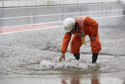 A marshal checks a drain cover overflowing with rain water