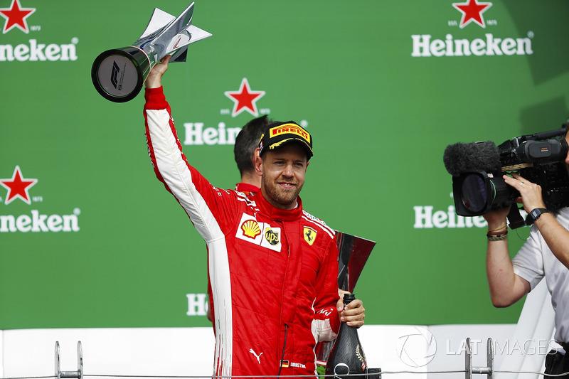 Sebastian Vettel, Ferrari, is filmed raising his winner's trophy on the podium