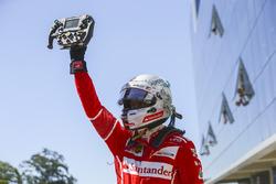 Race winner Sebastian Vettel, Ferrari, celebrates in Parc Ferme, with his steering wheel in his hand