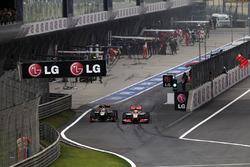 Kimi Raikkonen, Lotus E20 y Lewis Hamilton, McLaren MP4-27 batalla en pit lane