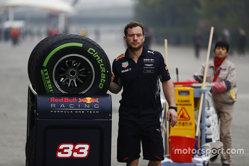 A Red Bull team member pushes a trolley of Pirelli tyres