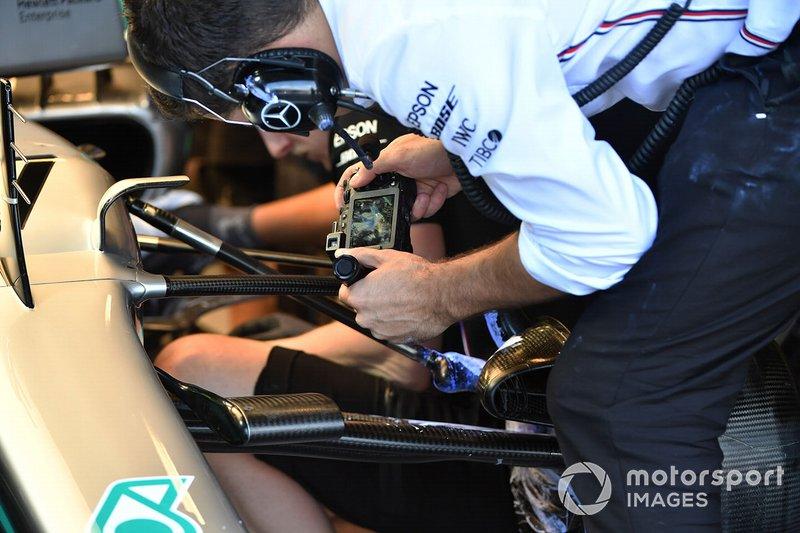 Un meccanico Mercedes a lavoro nel box con una macchina fotografica