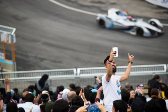 A fan takes a selfie with cars on track behind