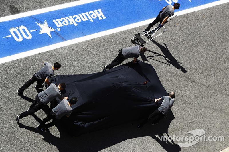 Механики McLaren толкают MCL32 Фернандо Алонсо в направлении боксов