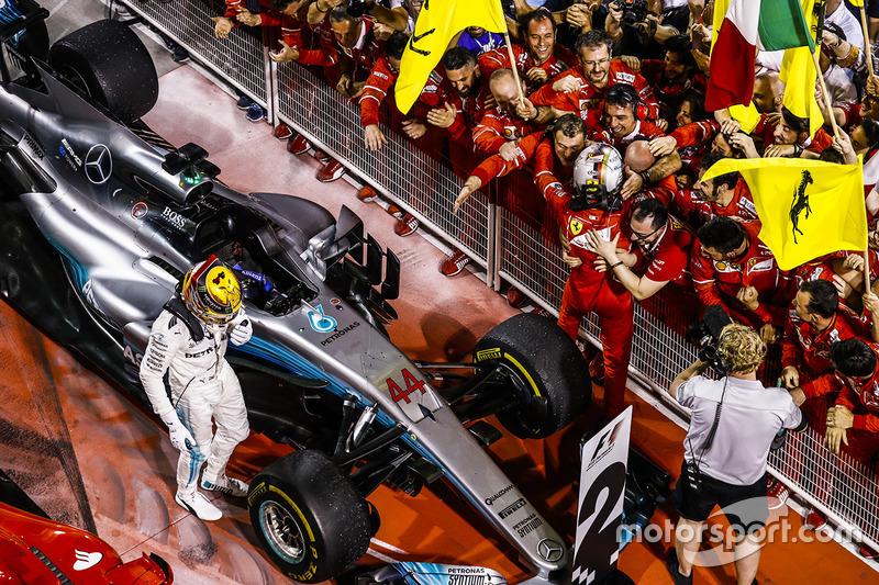 Le vainqueur Sebastian Vettel, Ferrari, fête sa victoire avec son équipe dans le parc fermé alors que le second Lewis Hamilton, Mercedes AMG F1, sort de sa voiture