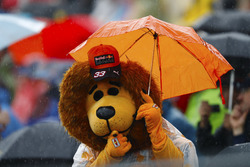 A Max Verstappen, Red Bull Racing, fan in a Lion mask holds an umbrella.