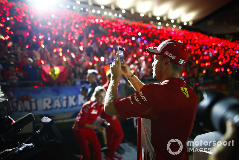 Sebastian Vettel, Ferrari, takes a photo of the gathered fans