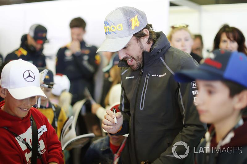 Fernando Alonso, McLaren, se encuentra con los niños de la grilla