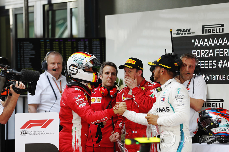 Winner Sebastian Vettel, Ferrari, is congratuled by second place Lewis Hamilton, Mercedes AMG F1, third place Kimi Raikkonen, Ferrari