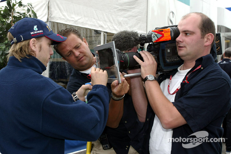 Nick Heidfeld signing an autograph on TV