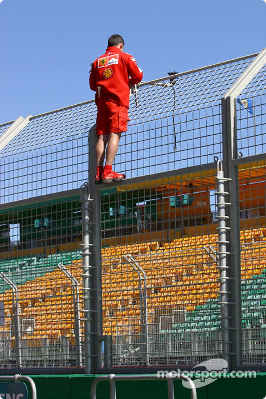 Ferrari crew member prepares pit wall area