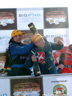 Marcos Ambrose helps team mate Russell Ingall celebrate