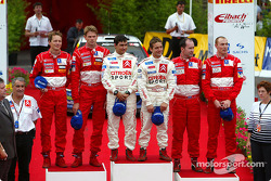 The podium: winner Sébastien Loeb and Daniel Elena, with Marcus Gronholm and Timo Rautiainen, and Richard Burns and Robert Reid