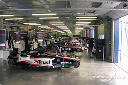 Eight Minardi F1x2 and two Minardi F1 cars lined up in the garage