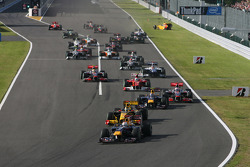 Sebastian Vettel, Red Bull Racing leads the start of the race and Vitaly Petrov, Renault F1 Team crashes