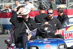 Team owner Ken Black aboard golf cart towing Greg Anderson in his Summit Racing Pontiac GXP