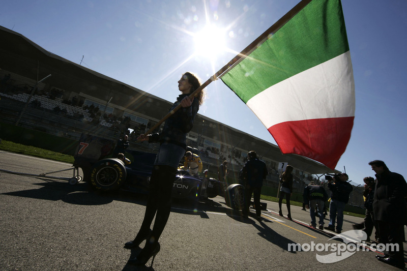 A grid girl with an Italian flag in front of Fairuz Fauzy