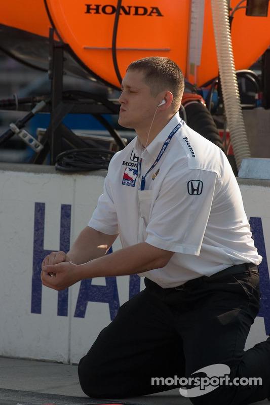 Un membre de l'équipe regarde l'arrêt au stand