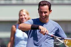 Helio Castroneves hits a backhand while WTA tennis star Anna Kournikova looks on during an exhibition tennis match at the Tennis Center at Crandon Park in Key Biscayne