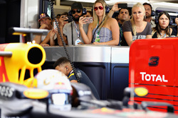 San Antonio Spurs basketball player Patty Mills watches the action in the Red Bull Racing garage with skier Lindsey Vonn