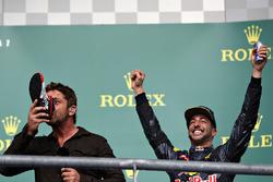 Podio: el actor Gerard Butler toma de la bota de Daniel Ricciardo, Red Bull Racing el tercer lugar