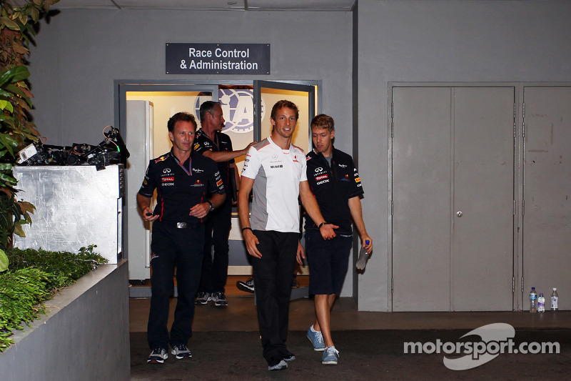 Jenson Button, McLaren en Sebastian Vettel, Red Bull Racing verlaten kantoor stewards