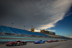 Cars wait to go on track under a menacing sky