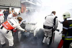 McLaren mechanics help extinguish the fire on Rubens Barrichello, Brawn GP BGP001 Mercedes at Parc Ferme