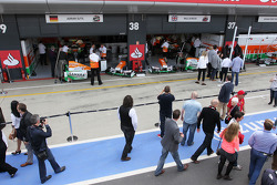 Sahara Force India F1 Team pit garages with fans in the pits