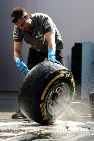 A Mercedes AMG F1 mechanic washes Pirelli tyres
