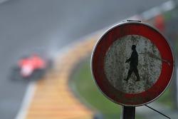 Carro da Marussia F1 Team, MR02, passa por uma antiga sinalzação de estrada