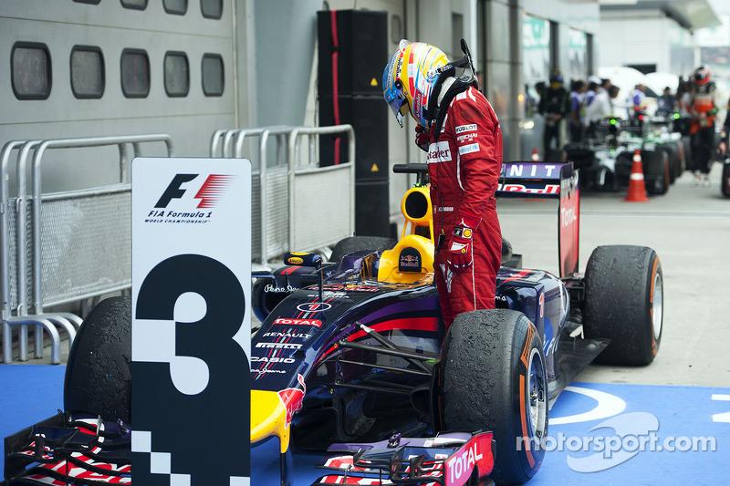 Fernando Alonso, Ferrari looks at the Red Bull Racing RB10 of Sebastian Vettel, Red Bull Racing in parc ferme