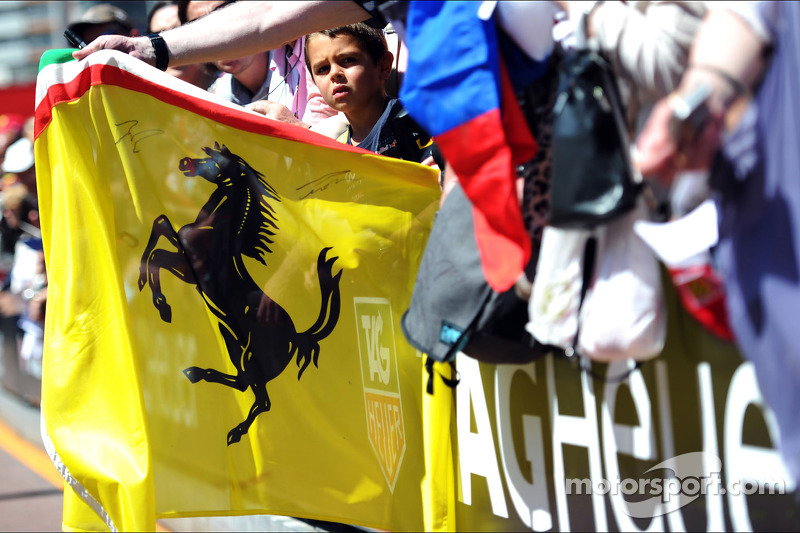 A Ferrari flag held by fans in the pit lane