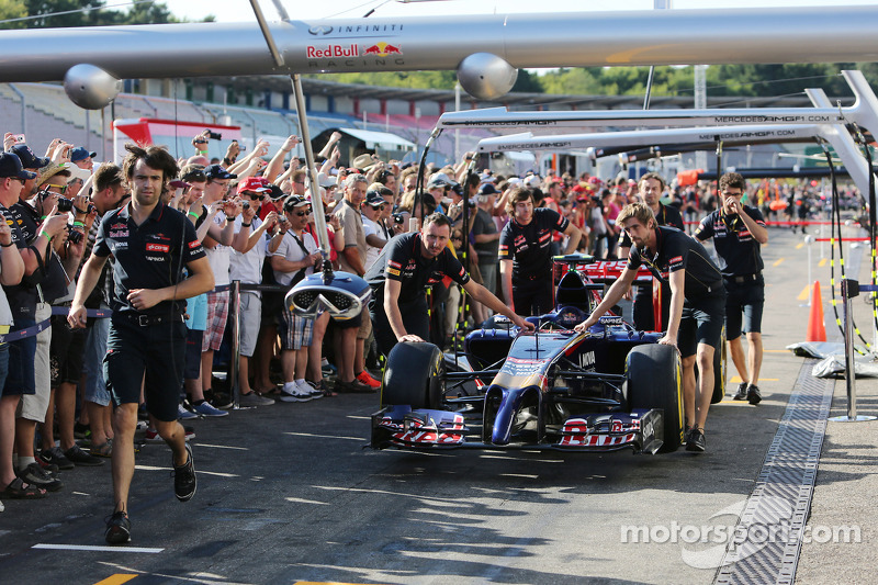 Fans in the pits as a Scuderia Toro Rosso STR9 is pushed down the pit lane