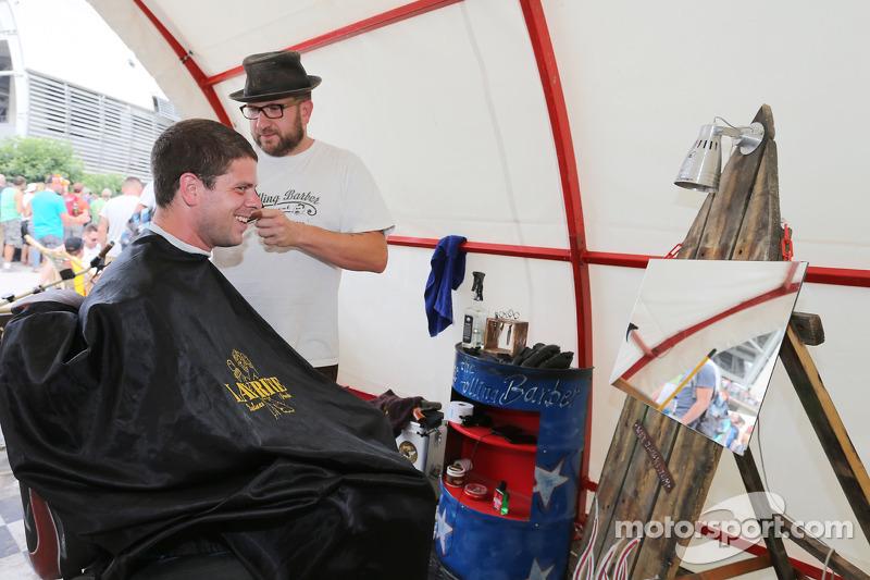 A fan has his hair cut