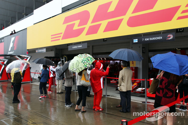 Fans in wet and rainy pit lane