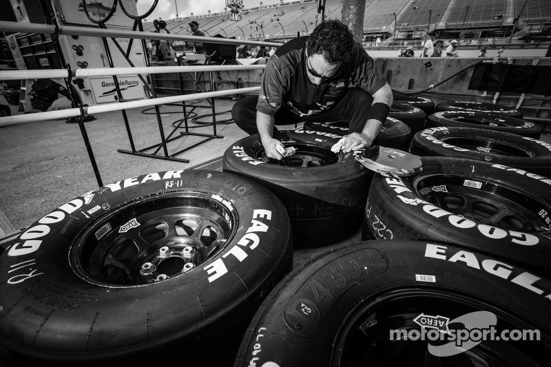 Mimebro del equipo de Denny Hamlin, Joe Gibbs Racing Toyota, prepara neumático