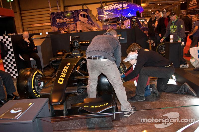 Anak laki-laki kecil membantu mengganti roda pada mobil balap