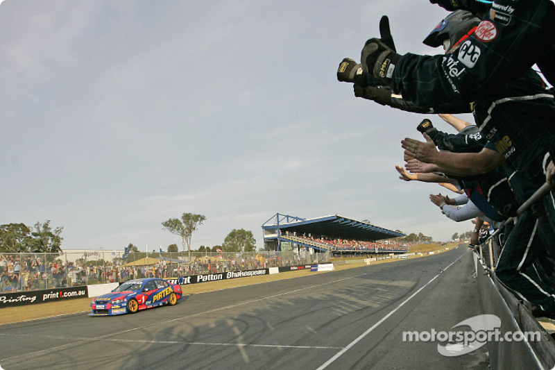 Marcos Ambrose takes the chequered flag and the Australian V8 Supercar Series 2004 championship